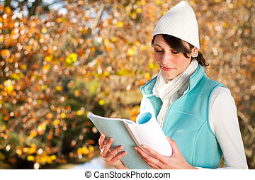 woman reading book in forest