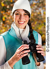 young woman using binoculars in autumn forest