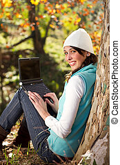 woman using laptop outdoors - beautiful woman working on...