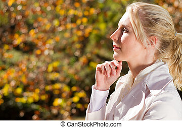 thoughtful blond woman in autumn forest