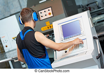 worker operating cnc punch press - worker at workshop...