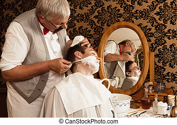 Antique shave - Antique barber shaving a customer with...