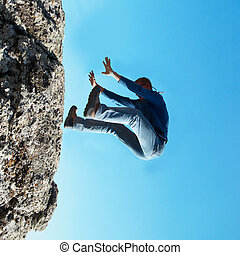 Falling down man from the rock with blue background