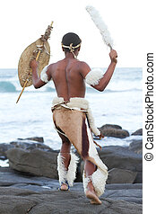 african tribesman on beach - african man dressing in...