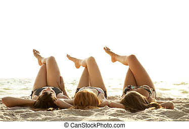 Three beautiful young girlfriends in bikini on the beach at...