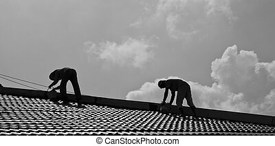 Roof Repairs - Two workmen repair roof in a hot afternoon