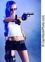 provocative - Shot of a sexy military woman posing with guns...
