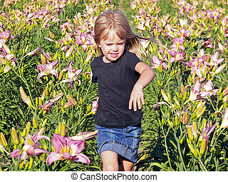 girl in day lilies - Little girl running in a day lily...