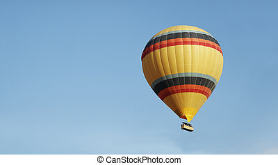 Yellow balloon color bands blue skies