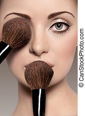 Portrait of a beautiful woman with a make up brush