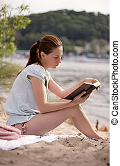 Young girl reading the book on the riverside - Young girl...