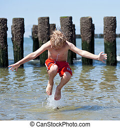 Boy jumps in sea - Small boy jumps in the shallow sea,...