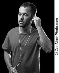 man listening to music with earphones, black and white photo