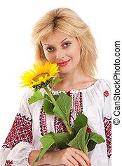 Woman wears Ukrainian dress is holding a sunflower - Woman...