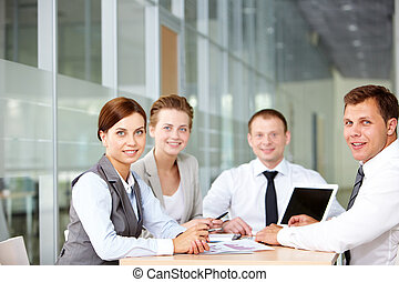 Successful team - A business team of four sitting at table...
