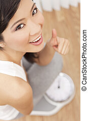 Asian Chinese Woman Thumbs Up Weighing Herself on Scales -...