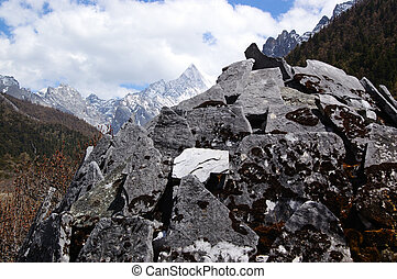 Tibetan mani stones by snow mountain in Daocheng,Sichuan...