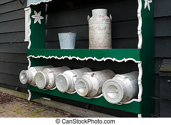 milk cans - old fashioned milk cans against a wall