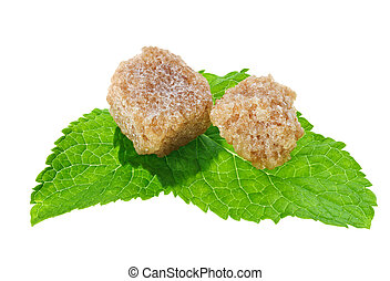 Two brown lump cane sugar cubes over peppermint leaves,...
