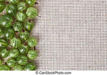 Many gooseberry fruits on gray linen table cloth with copy...