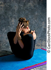 A brown haired caucasian woman is doing yoga exercise, Womb Embryo Posture or Garbha Pindasana posture studio on yoga mat with grey mottled background.