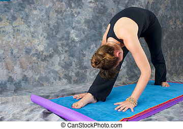 A brown haired caucasian woman is doing yoga exercise, Pyramid Pose or Parsvottonasana posture  on yoga mat in studio with mottled background.