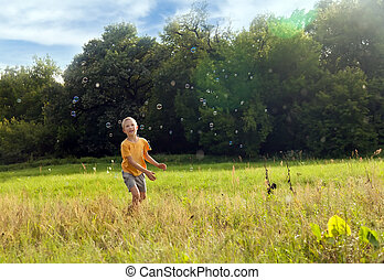 Small boy catching soap bubbles in the green field