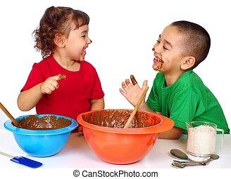 kids having fun baking - boy and girl having a playful time...