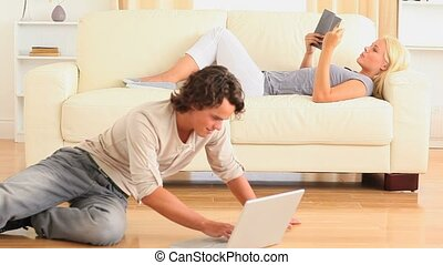 Woman reading a book and man surfing the web in the...