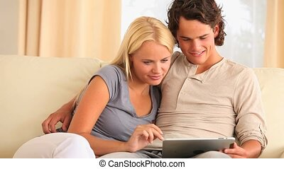Couple on sofa with a tablet in their livingroom