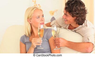 Couple toasting with Champagne in their livingroom