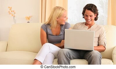 Couple sitting on a sofa searching the web in their...