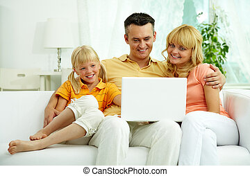 Using laptop - Image of friendly family sitting on the sofa...