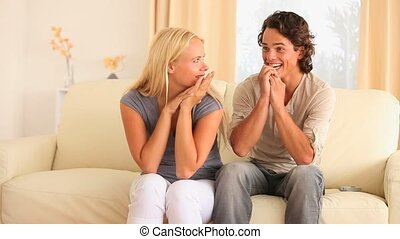 Excited couple sitting on a sofa in their livingroom