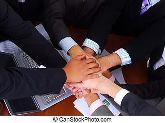 group of business people making a pile of hands in a light...