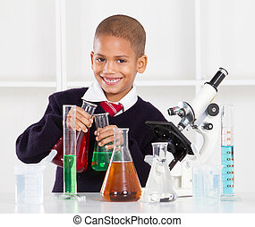 happy primary schoolboy in science lab
