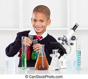 happy primary schoolboy in science lab