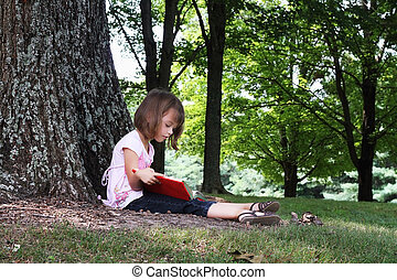 Child Reading A Book - Little girl sits outdoors under a...