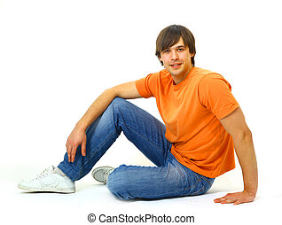 Portrait of a casual young satisfied man sitting relaxed...