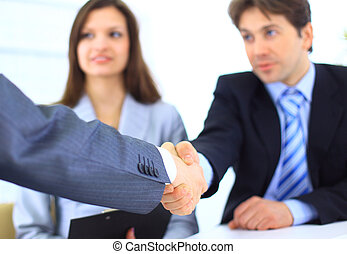 Two Business men shaking hands while team smiling at office