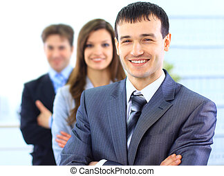 Portrait of a successful businessman standing with arms crossed and colleagues in background