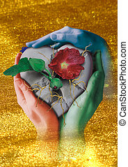 heart - A broken stone heart in three hands with new buds,...
