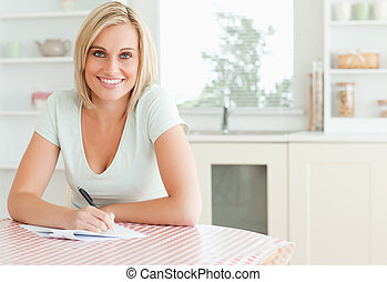 Charming woman proof-reading a text looks into camera in the...
