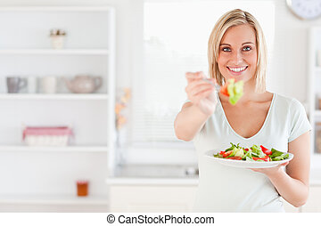 Close up of a good looking woman eating salad