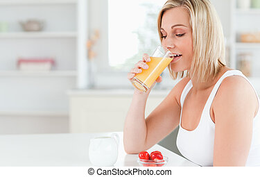 Woman sitting at a table drinking orange juice in the...