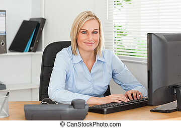 Working woman in front of a screen looks into camera in an...