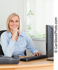 Working smiling woman in front of a screen looking into...