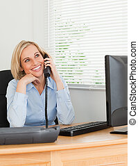 Cheerful businesswoman on phone looks at the ceiling of her...