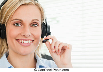 Close up of a smiling businesswoman with headset looking into camera in her office