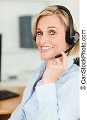 Portrait of a smiling businesswoman with headset lookinginto camera in her office